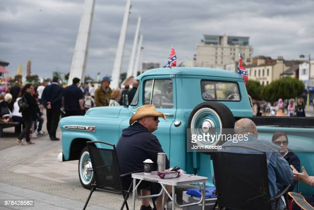 People sit by their Chevrolet Apache 31 American pickup truck during the Southend Classic Car Show along the seafront on June 17 2018 in Southend on...