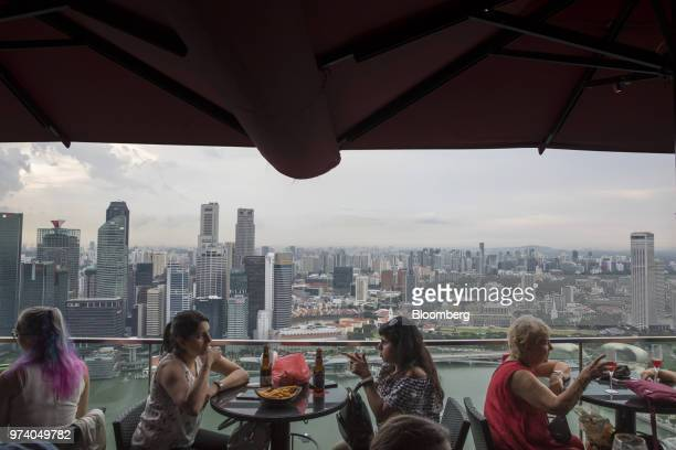 People sit dining at a restaurant at the Marina Bay Sands hotel as commercial buildings stand in the central business district left of Singapore on...