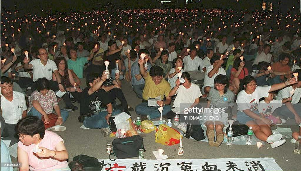 People sit during a candlelight vigil in Victoria Park 04 June in commemoration of the violent crackdown on pro-democracy protestors in 1989 in Tiananmen Square in Beijing, China. Thousands crowded the park and sang pro-democracy songs during the yearly rally.