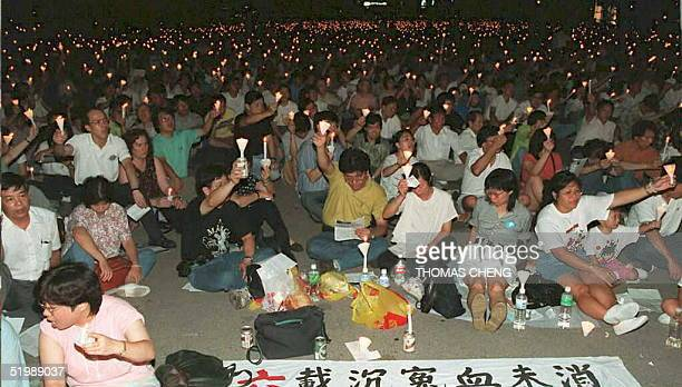 People sit during a candlelight vigil in Victoria Park 04 June in commemoration of the violent crackdown on prodemocracy protestors in 1989 in...