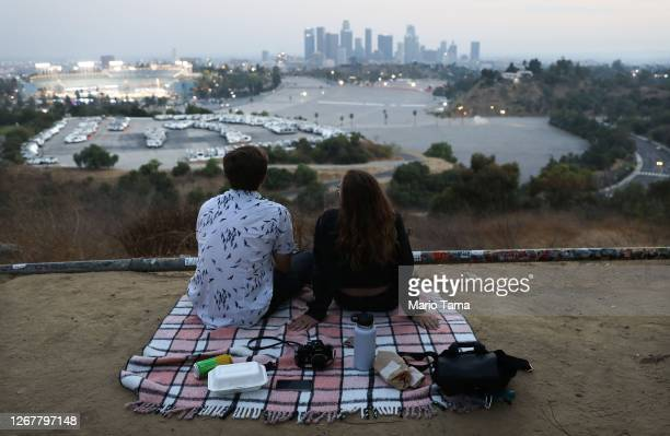 People sit for a picnic on a hillside overlooking Dodger Stadium and downtown Los Angeles during a game between the Colorado Rockies and the Los...