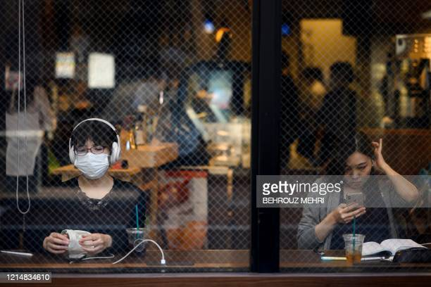 People sit in a cafe in Sugamo district of Tokyo on Mau 24, 2020. - Prime Minister Shinzo Abe on May 21, 2020 lifted a state of emergency in several...