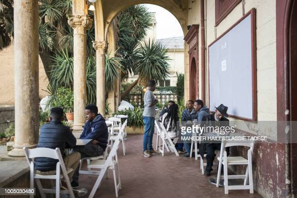 People sit in a cafe of the Eritrean capital Asmara on July 21, 2018. - Located at over 2000 metres above sea level, the capital of Eritrea developed...