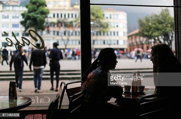 People sit in a cafe on September 29 2016 in Bogota Colombia Colombians will cast their ballots on October 2 in a final referendum on a peace accord...