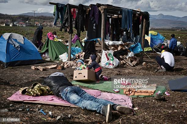 TOPSHOT People sit in a makeshift camp at the Greek Macedonian borders near the village of Idomeni on March 8 where thousands of refugees and...