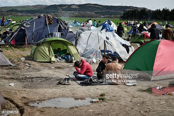 People sit in a makeshift camp at the Greek Macedonian borders near the village of Idomeni on March 8 where thousands of refugees and migrants are...