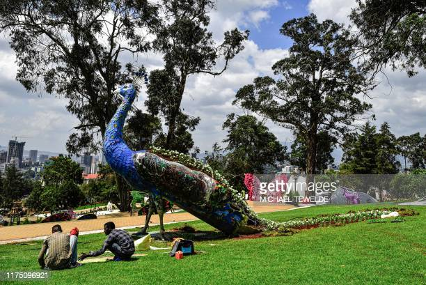 People sit in a part of new Unity Park former Emperor's palace compound which has been restored before it opens to the public in Addis Ababa on...