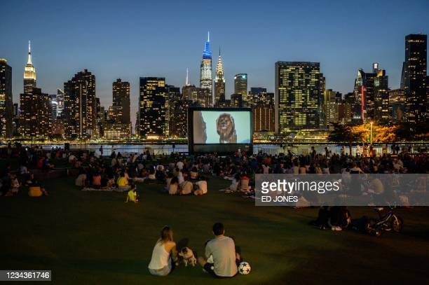 People sit in a public park as they watch an outdoor screening of the Lion King before the Manhattan skyline in the Long Island City, New York on...