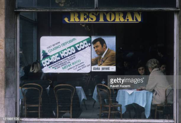 People sit in a restaurant in Belgrade, Serbia, with a poster of Montenegrin politician Slavko Perovic in the window, 23rd December 1986.