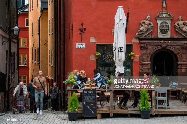 People sit in a restaurant in Stockholm on May 29 amid the coronavirus COVID-19 pandemic. - Sweden's two biggest opposition parties called Friday for...