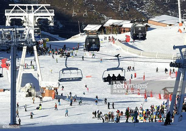 People sit in a ski lift as others ski down a slope on the opening weekend of the ski season on November 26 2016 at the Val Thorens ski resort in the...