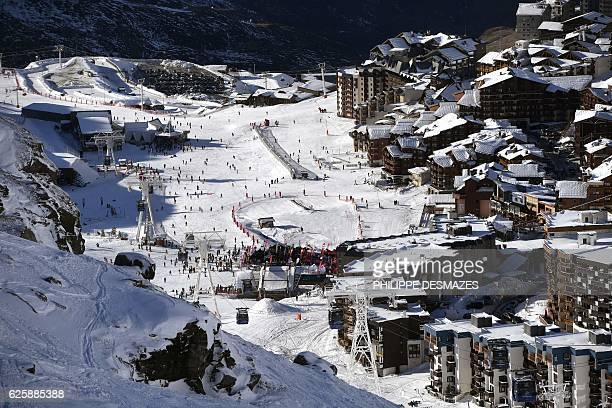 People sit in a ski lift as others ski down a slope on the opening weekend of the ski season on November 26 2016 at Val Thorens ski resort in the...