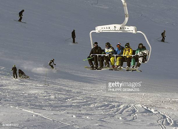 People sit in a ski lift on the opening weekend of the ski season on November 26 2016 at Val Thorens ski resort in the French Alps / AFP / PHILIPPE...