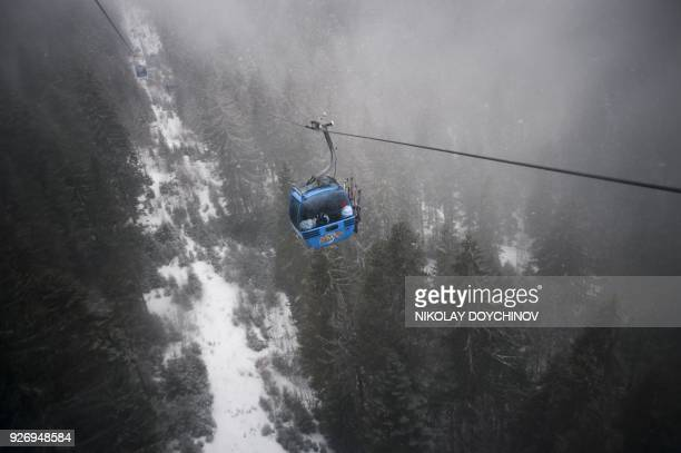 People sit in a telecabin on February 10 2017 in the Banderishka polyana ski resort near Bansko Unlimited SkiFun promises a pamphlet touting the...