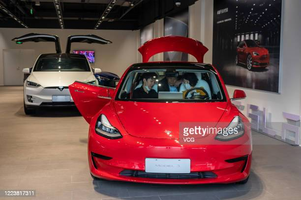 People sit in a Tesla Model 3 car at the first Tesla Center in Shanghai on May 9 2020 in Shanghai China