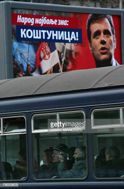 People sit in a tram backdropped by a poster of Vojislav Kostunica the leader of the DSS in Belgrade 17 January 2006 Parliamentary elections in...