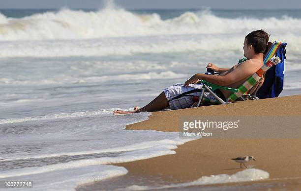 People sit in beach chairs watching the high surf caused approaching hurricane Earl, on September 1, 2010 in Kitty Hawk, North Carolina. A hurricane...