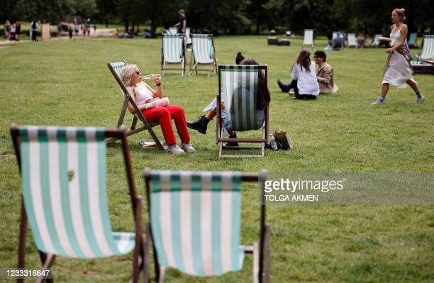 People sit in deck chairs as they enjoy the sunshine in Green Park in central London on June 7, 2021. - The Delta variant of the coronavirus, first...