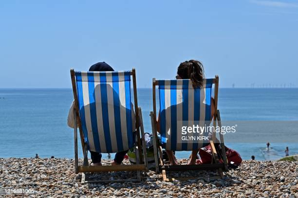People sit in deckchairs as they enjoy the sunshine on the beach in Brighton on the south coast of England on June 2, 2020 following a further...