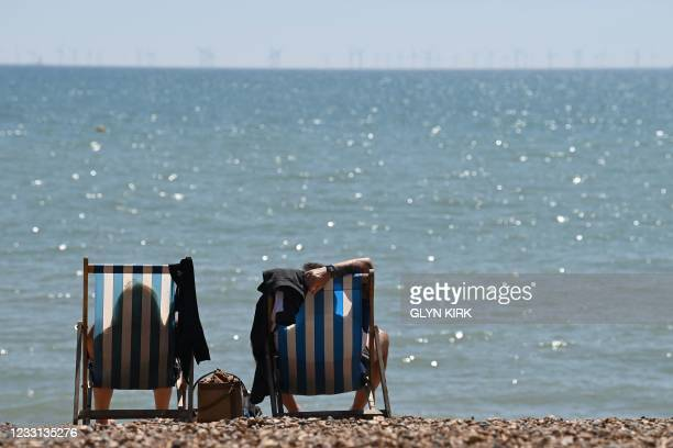 People sit in deckchairs looking out onto the channel on Brighton beach in Brighton, southern England as temperatures rise across the country on May...
