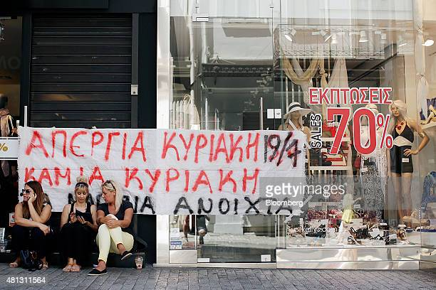 People sit in front of a banner taped to the front of a clothing store to demonstrate against stores opening and trading on Sundays in Athens Greece...