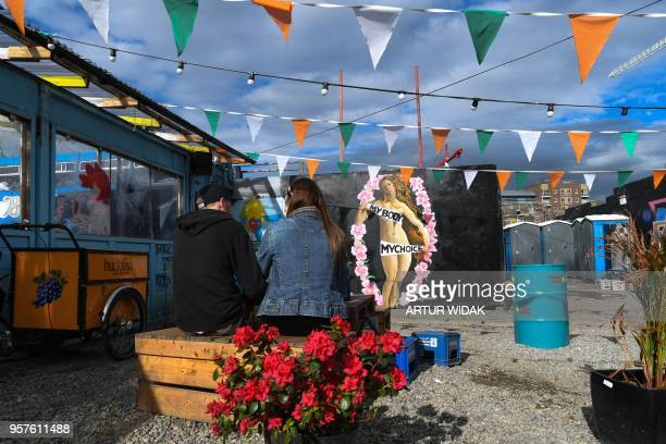 People sit in front of a pro-choice mural relating to the laws regarding abortion in Dublin on May 11, 2018 ahead of the referendum. - Ireland will...