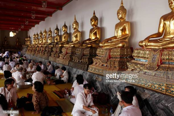 People sit in front of golden buddha's at Wat Pho temple of the Reclining Buddha on October 30 2012 in Bangkok Thailand Teams from all over the world...