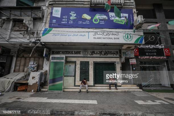 People sit in front of Islamic National Bank as shops closed in Gaza City Gaza on October 01 2018 during a general strike to protest against Israeli...