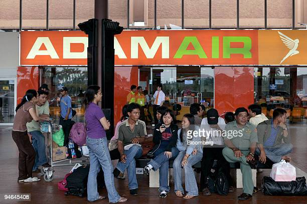 People sit in front of the Adam Air ticketing office at SoekarnoHatta International Airport in Cengkareng near Jakarta Indonesia on Monday April 16...