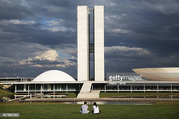 People sit in front of the Brazilian National Congress building on October 27 2014 in Brasilia Brazil Brazil's leftwing President Dilma Rousseff was...