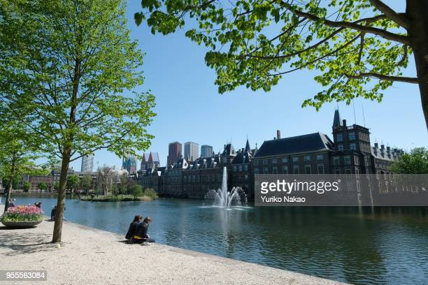 People sit in front of the Hofvijver or 'Court Pond' of Binnenhof on May 3 in The Hague Netherlands