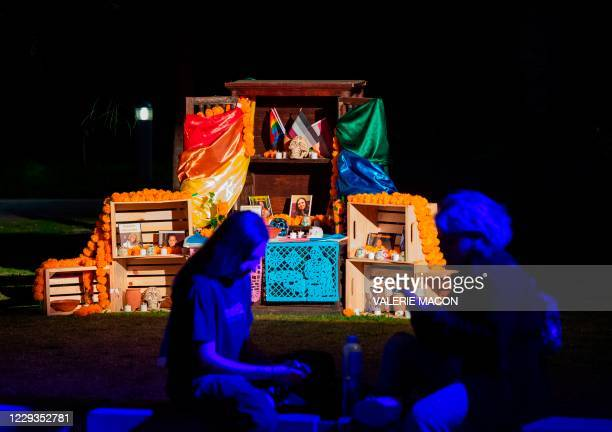 """People sit in front of the """"Mi Estori: Artist Collective"""" altar honoring the victims of homophobic and transphobic crimes during a socially distant..."""