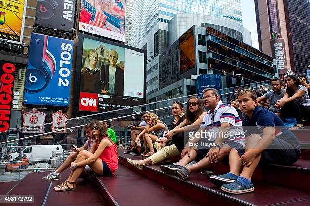 People sit in front of works of art displayed on digital billboards in Times Square August 4 2014 in New York City A total of 58 classic and...