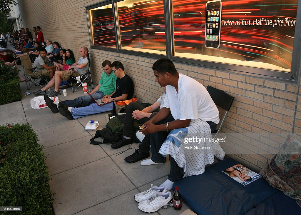 People Sit In Line After Waiting All Night At The Apple Store July 11