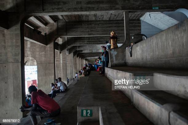 People sit in rows of sits as they attend the Eyo festival at the Tafawa Balewa Square in Lagos on May 20 2017 The whiteclad Eyo masquerades...