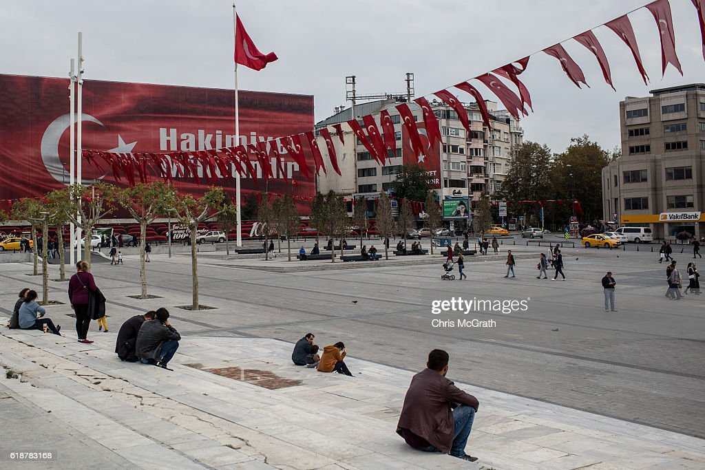 People sit in Taksim square in front of a billboard posted after the failed coup attempt displaying the words Hakimiyet Milletindir (Sovereignty belongs to the people/nation) on October 23, 2016 in Istanbul, Turkey. Since the failed coup attempt on July 15, 2016 which saw 240 people killed including 173 civilians, Turkish authorities initiated a state of emergency, leading to an unprecedented crackdown on individuals and organizations with links to US-based cleric Fethullah Gulen and his organization blamed for instigating the uprising. The purge, targeting teachers, journalists, soldiers, judges, academics, police, military leaders, schools and universities has so far seen approximately 100,000 people dismissed, 70,000 detained, 32,000 arrested, 130 media outlets closed and some 15 universities shuttered. The failed coup and subsequent purge only appears to have further bolstered the president's popularity and increased nationalism across the country with July 15th having been marked as a new national holiday. Turkish flags, already prominently displaying all over have increased in numbers, as well as posters of those killed fighting the coup plotters appearing in train stations and public squares. The Bosphorus Bridge in Istanbul, which saw heavy fighting during the coup has been renamed the '15th July Martyr's Bridge'. These changes, follow a year of instability in the country with constant terrorist attacks, an economic downturn, plummeting tourism, and a refugee crisis, all contributing to Turkish society undergoing its most dramatic restructuring in decades.
