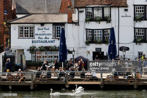 People sit in the afternoon sunshine in the garden of The Angel on the Bridge pub in Henley-on-Thames, west of London on April 12, 2021 as...