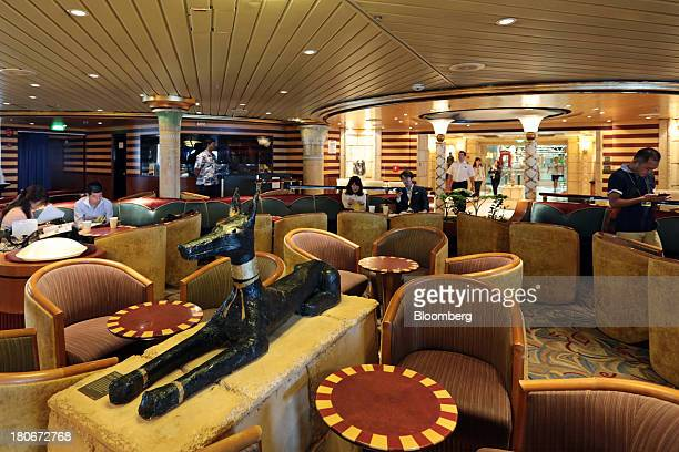 People sit in the 'Cleopatra's Needle' lounge aboard the Royal Caribbean Cruises Ltd's Voyager of the Seas berthed at the Ohi wharf in Tokyo Japan on...