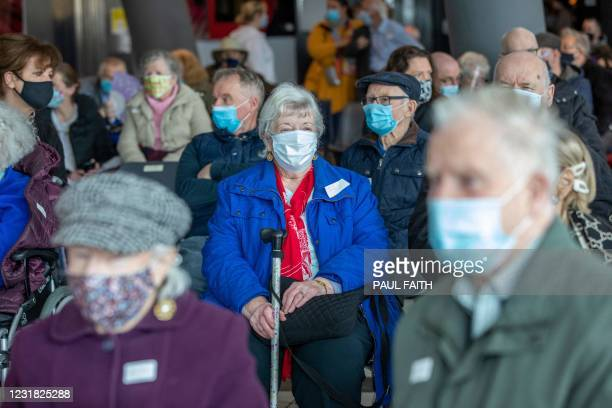 People sit in the post-vaccination waiting area after receiving the Pfizer/BioNTech Covid-19 vaccine at a vaccination centre at the Helix on Dublin...