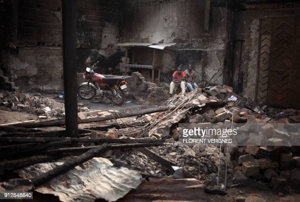 TOPSHOT People sit in the ruins of a market after a blaze which damaged 47 shops on January 17 in Bangui's predominantly Muslim PK5 quarter on...