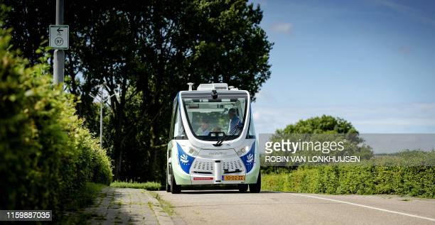 People sit in the selfdriving shuttle bus as it drives down a roach on August 5 in Drimmelen The bus is an experiment and carries passengers in the...