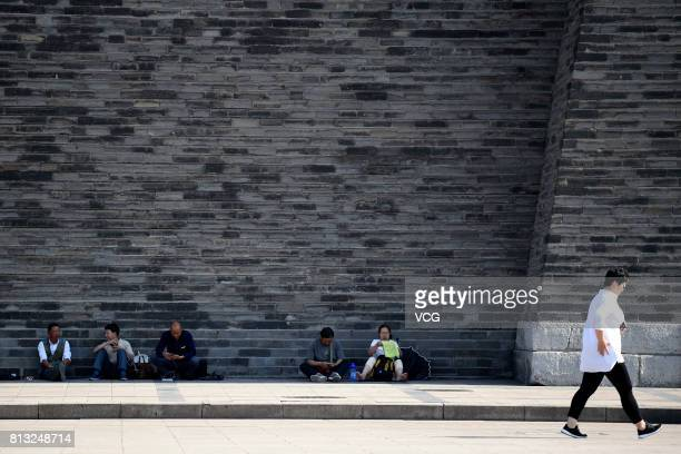 People sit in the shade by the wall on July 12 2017 in Beijing China The dog days of summer start from July 12 in China