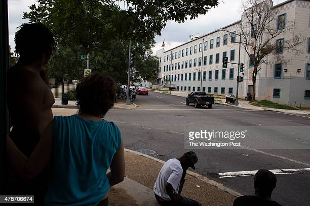 People sit in the shade on the corner of 2nd and D streets Northwest in Washington, DC, on June 20, 2015. Officials at the nearby Community for...