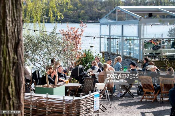 People sit in the spring sun at an outdoor restaurant in Stockholm Sweden on April 26 amid the novel coronavirus COVID19 pandemic Stockholm health...