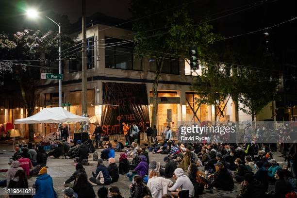 People sit in the street while watching a documentary film screening outside of the Seattle Police Departments East Precinct on June 9, 2020 in...