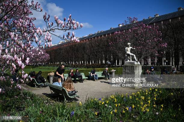 People sit in the sun in the Palais Royal garden in Paris on March 20 on the first day of a new lockdown in France aimed to curb the spread of the...
