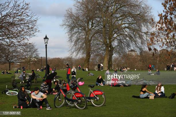 People sit in the sunshine at Hyde Park on February 21, 2021 in London, England. The British government is expected to announce tomorrow its plans...
