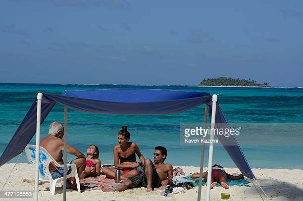 People sit in the sunshine on the sandy beach on January 24 2014 in San Andres Colombia Colombia has a territorial dispute with Nicaragua regarding...