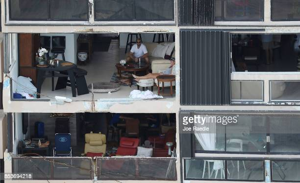 People sit in their apartment after the window was blown out by the winds of Hurricane Maria as it passed through the area on September 25 2017 in...