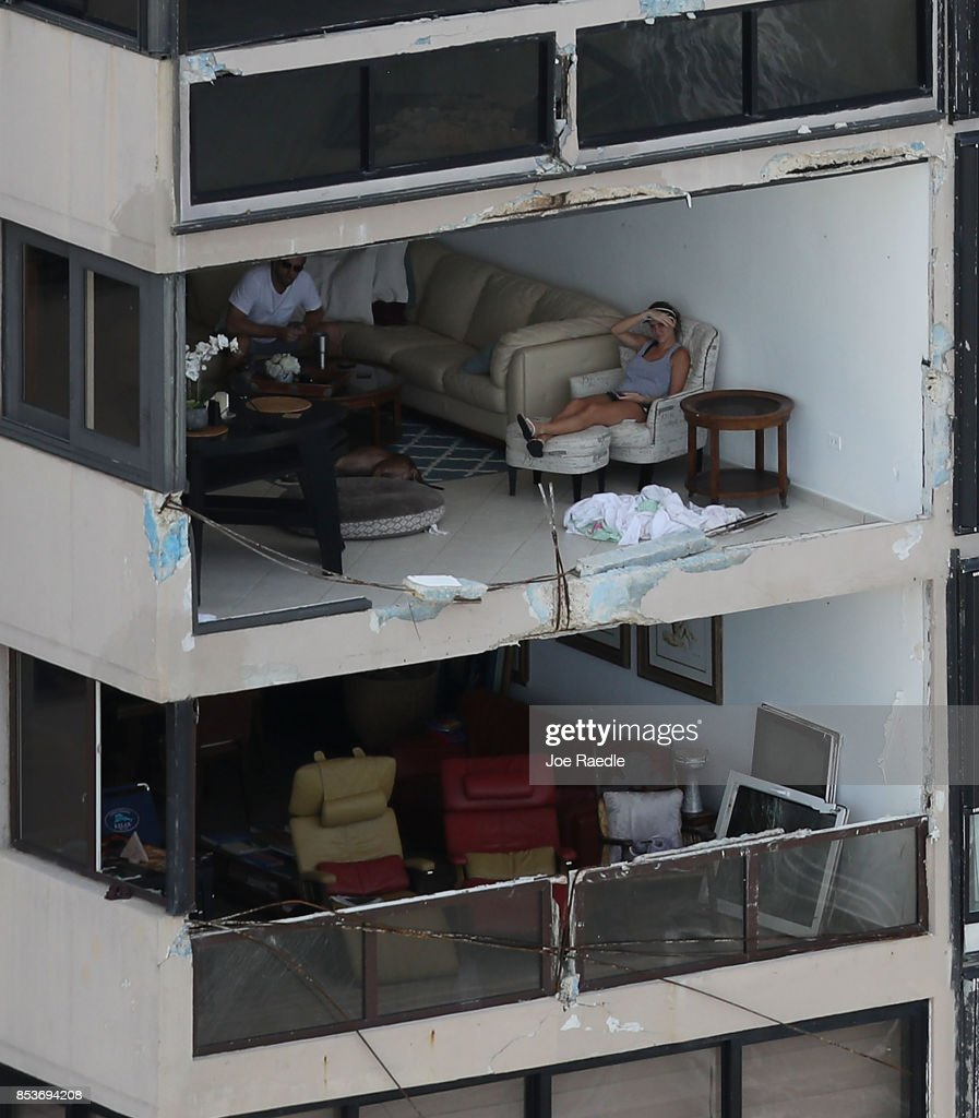 People sit in their apartment with the window blown out by the winds of Hurricane Maria as it passed through the area last week on September 25, 2017 in San Juan Puerto Rico. Maria left widespread damage across Puerto Rico, with virtually the whole island without power or cell service.